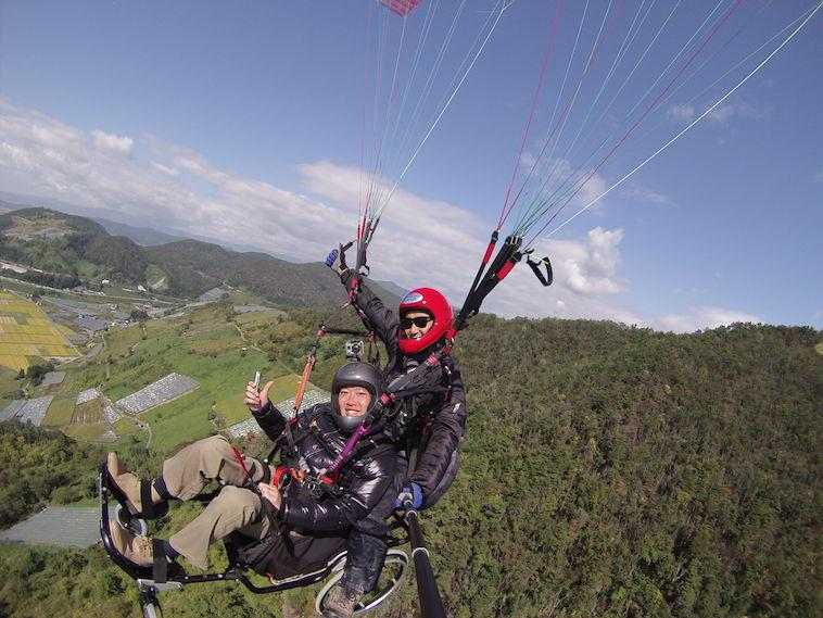 【写真】車椅子でパラグライダーをする男性と、一緒に飛ぶ男性。雄大な景色をバックに笑顔で写っている。