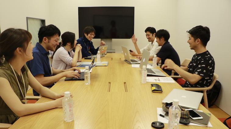 【写真】長机に向き合って座るプロジェクトチーム。和やかな空気が流れている。