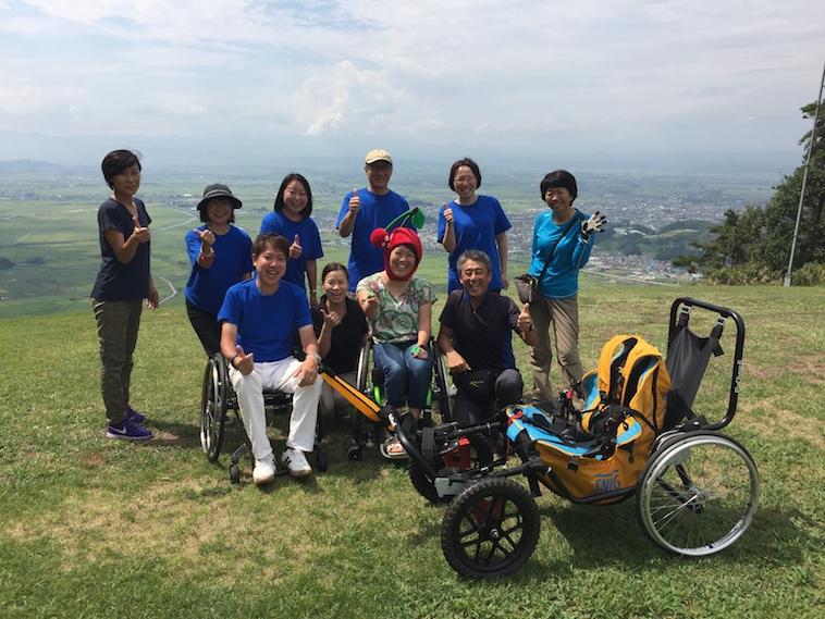 【写真】かとうさんと車椅子のフライトサポートを行う仲間立ち。楽しげな空気が流れている。