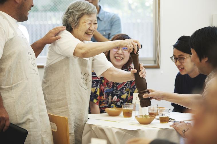 【写真】大きなペッパーミルを使い、お客さんの目の前で料理に胡椒をかけるスタッフ。周りのスタッフもお客さんも笑顔で見守っている。