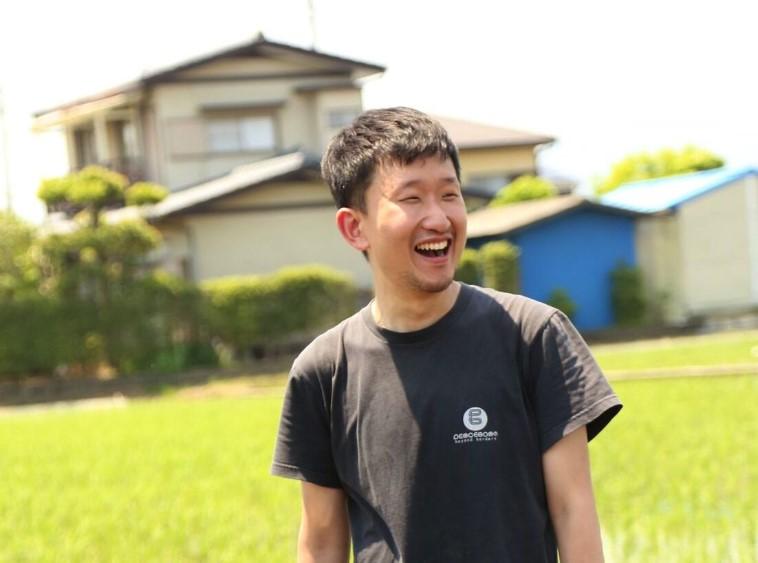 【写真】笑顔で田んぼの前に立つおおたなおきさん。