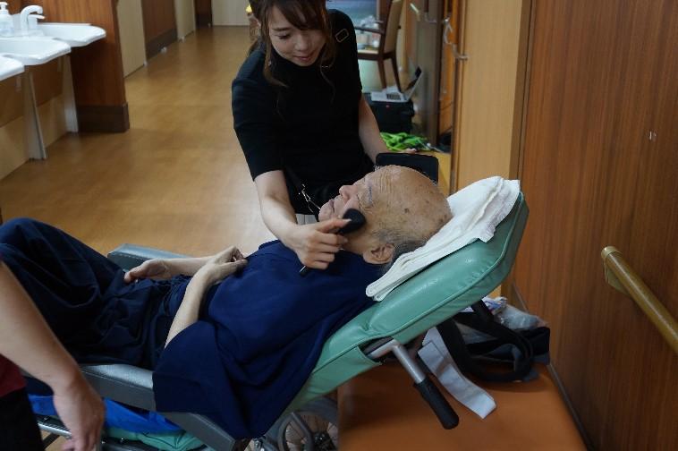 【写真】横になるおじいさんの顔に、微笑みながら化粧筆をそっとのせるスタッフ。