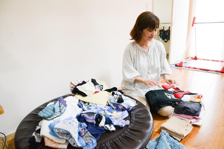 【写真】スタッフの方が微笑んで洗濯物をたたんでいる