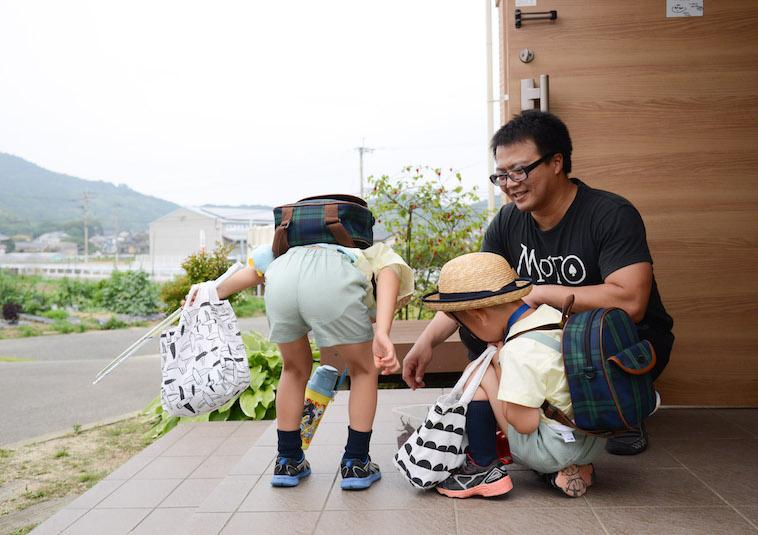 【写真】笑顔のたはらまさのりさんとカブトムシを興味津々に見ている二人の子ども