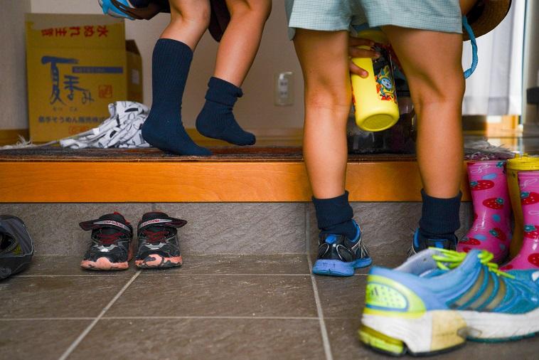 【写真】玄関で靴を脱いで元気に家に上がる子どもたち