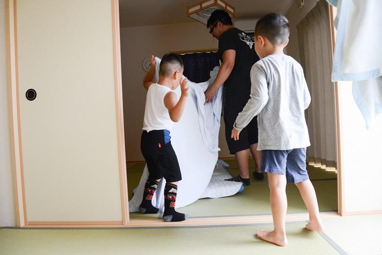 【写真】畳の部屋で布団をたたむたはらまさのりさんと子どもたち
