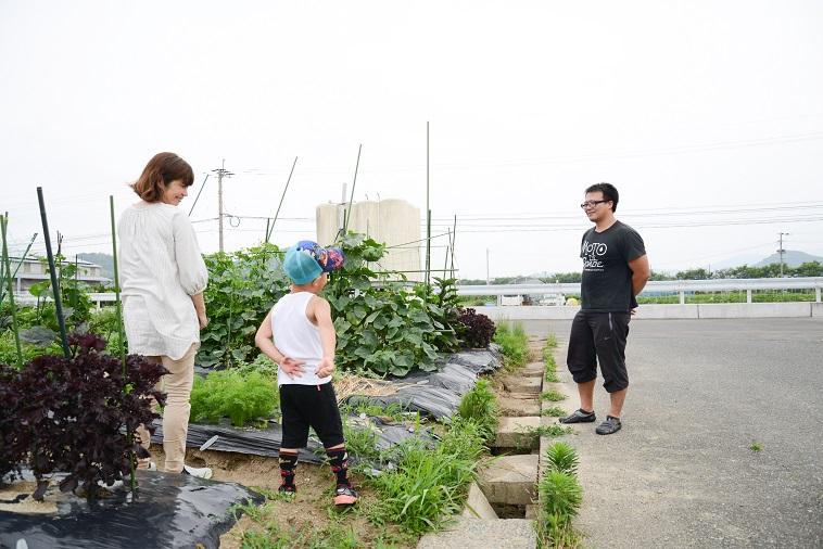 【写真】畑で楽しそうに話すたはらまさのりさんと子どもと子どもの村福岡のスタッフ