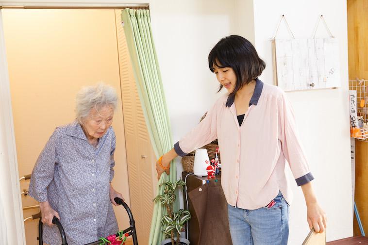 【写真】前に進もうとするおばあさんのために、カーテンを開けて進行をフォローするたかすさん
