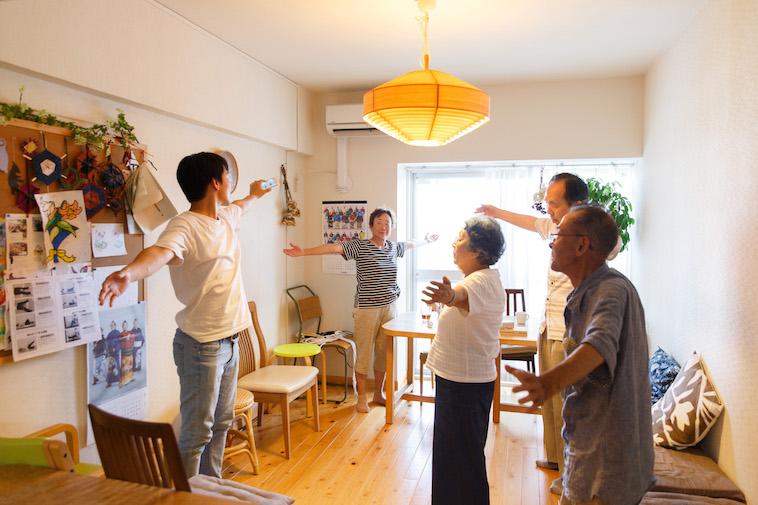 【写真】あたたかな雰囲気の室内で、おじいさんとおばあさんがスタッフとともに体操を行なっている
