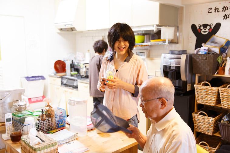 【写真】キッチンスペースに腰掛けるおじいさんに、笑顔で話しかけるたかすさん