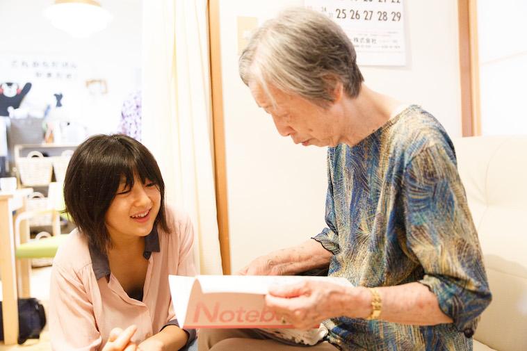 【写真】おばあさんの開いた大学ノートを覗き込む、たかすさん
