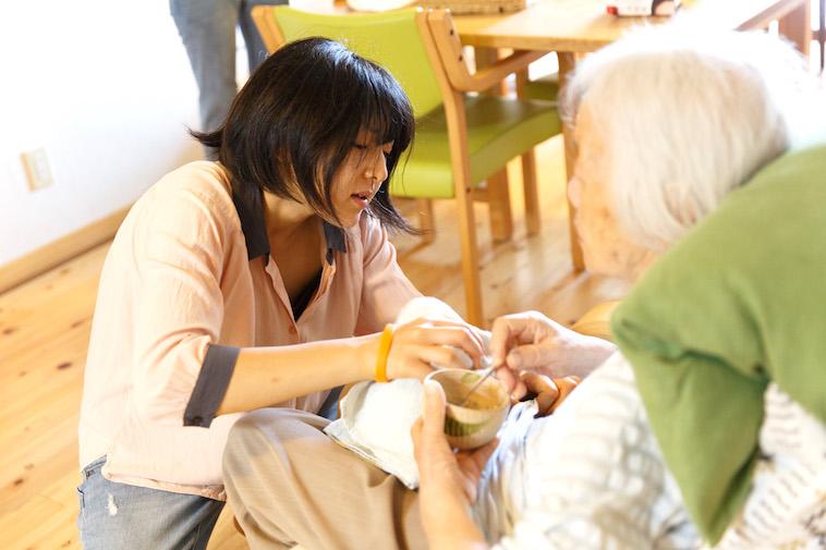 【写真】おばあさんの食事介助を丁寧に行うたかすさん