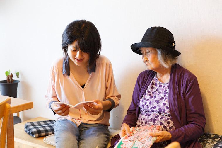 【写真】おばあさんの隣に座り、小さなノートを開いて覗き込むたかすさん