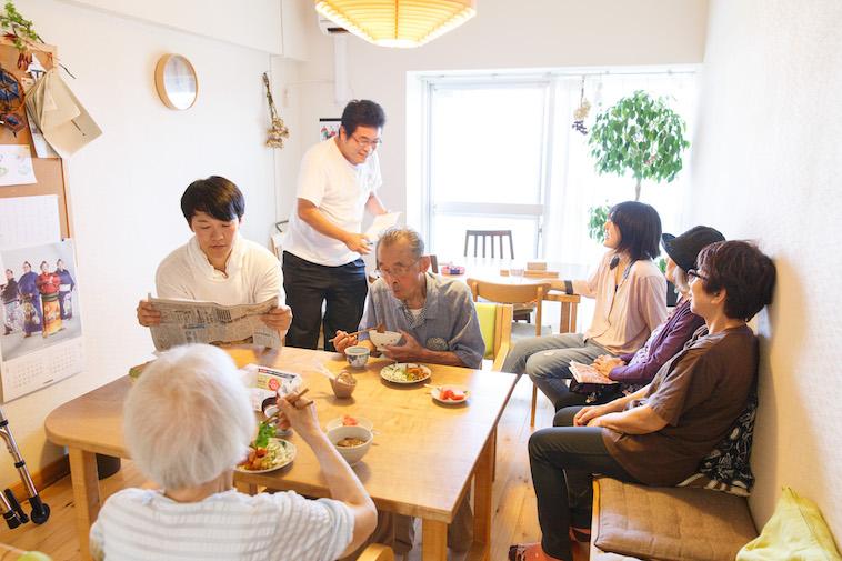【写真】ぐるんとびーの様子。おじいさんやおばあさんが食事をしている横で、スタッフがミーティングを行なっている