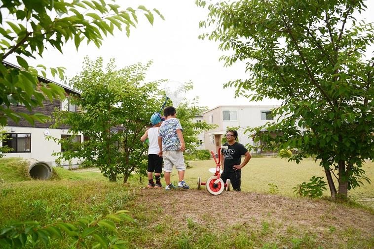 【写真】外に出て遊んでいるたはらまさのりさんと子どもたち。子どもは虫取り網を持っていて楽しそうだ