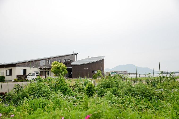 【写真】緑の畑の奥にシックな木製の住宅がある