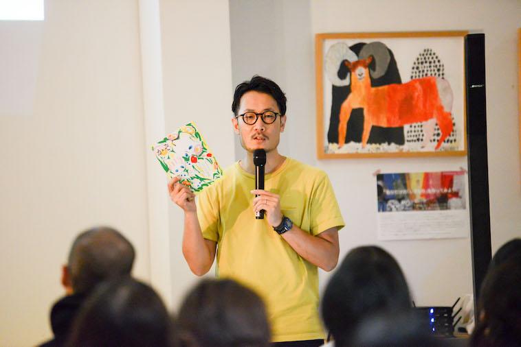 【写真】子どもの村が発行した冊子を片手に参加者の前で語る、たきたさん