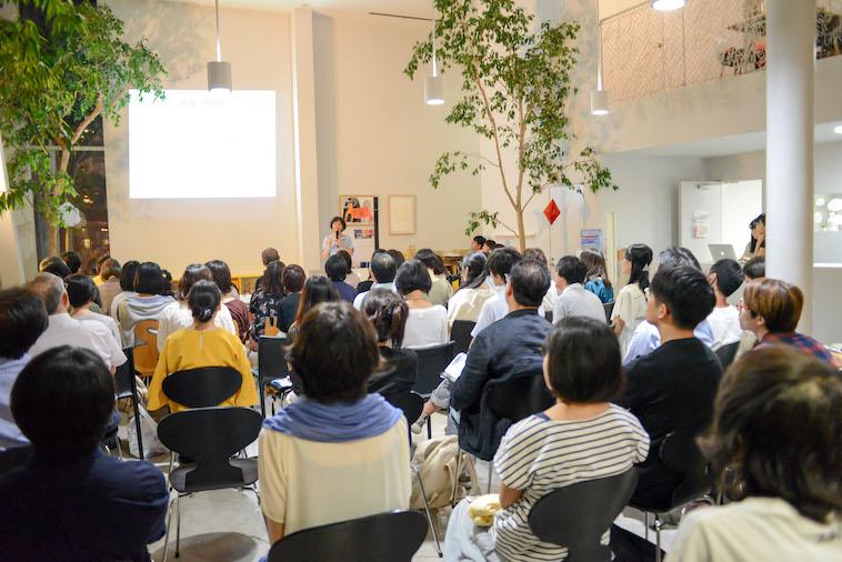 【写真】会場全体写真。スライドを見ながら、参加者のみなさんが登壇者の話を聞いている