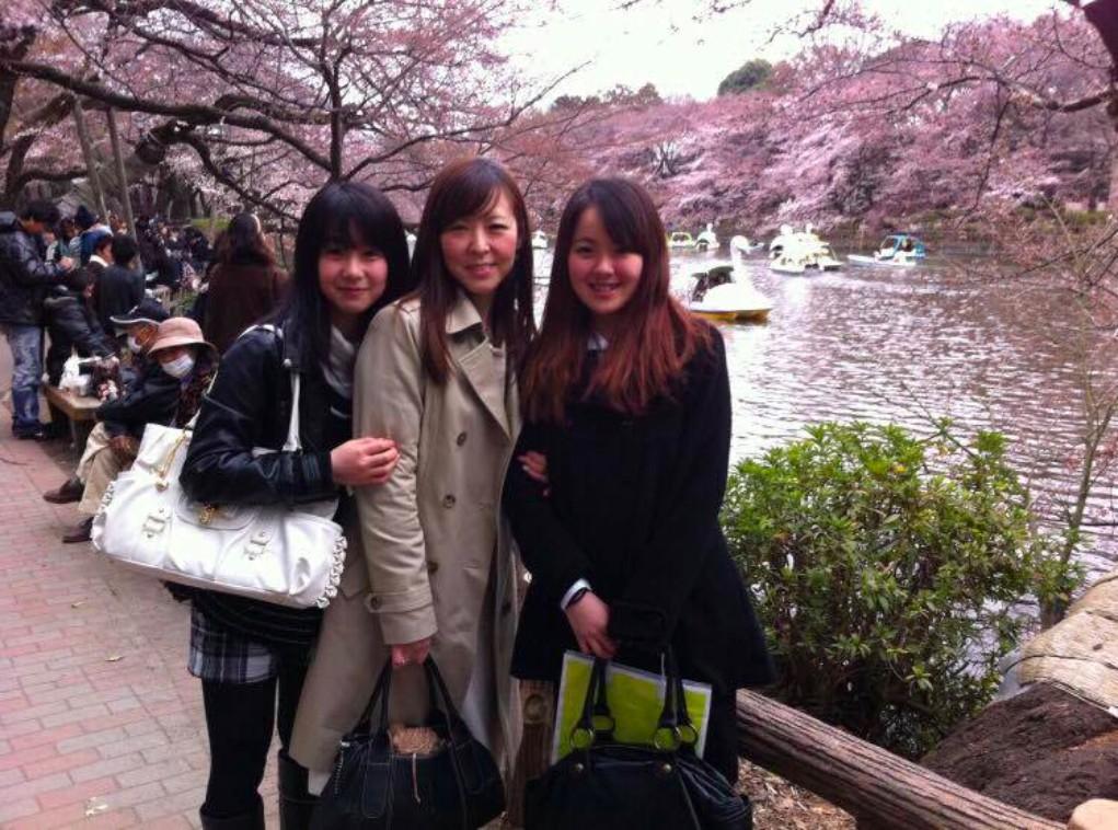 【写真】笑顔の二人の娘さんとくらさわなつこさん。桜の花びらが川面に浮いている