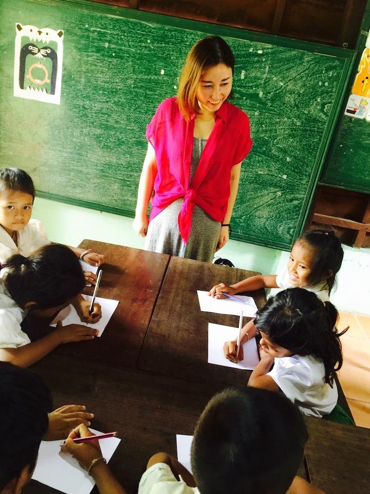 【写真】カンボジアの子どもたちへ美術を教えるくつなさん。ノートを取っている子も多く、真剣な様子が伝わってくる。