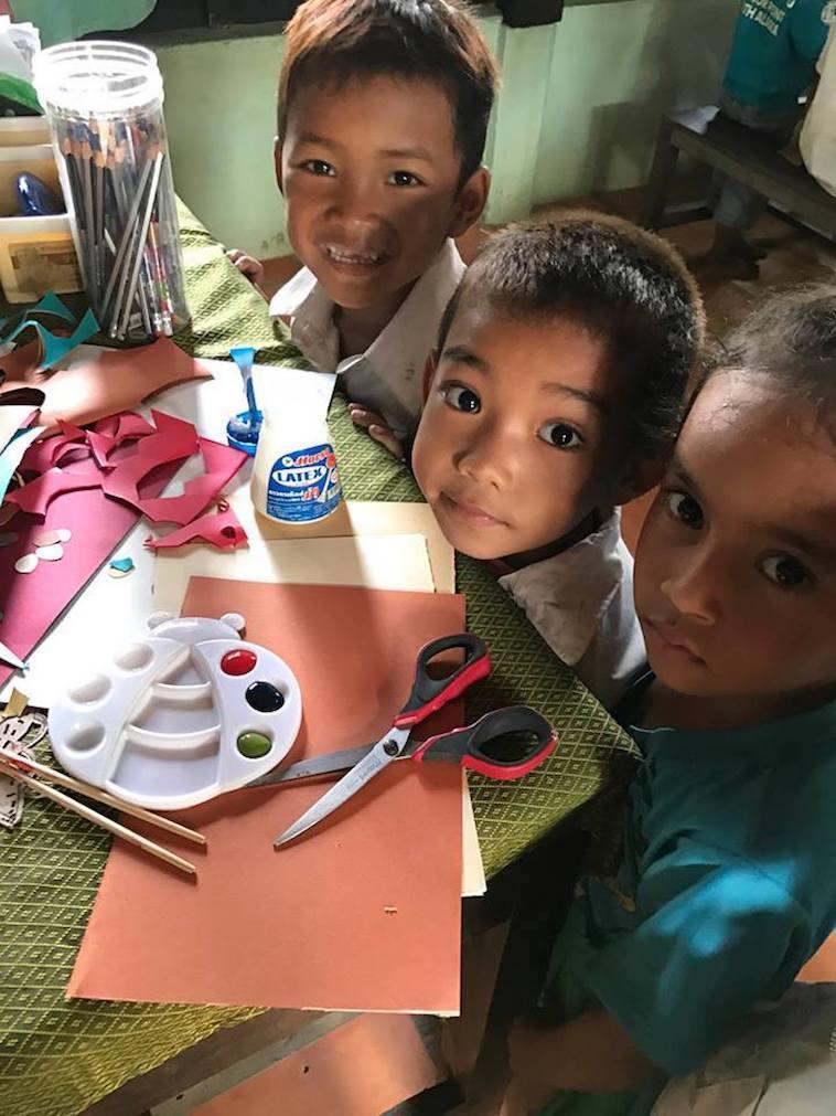 【写真】絵の具や色鉛筆、画用紙の前でカメラに笑顔を見せる生徒たち。