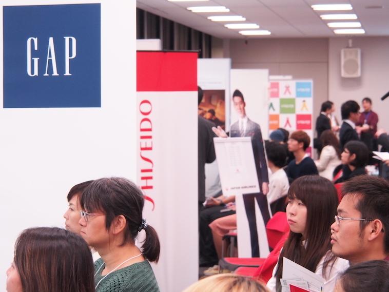 【写真】ブースでの企業の話に、真剣に耳を傾けるイベント参加者たち。