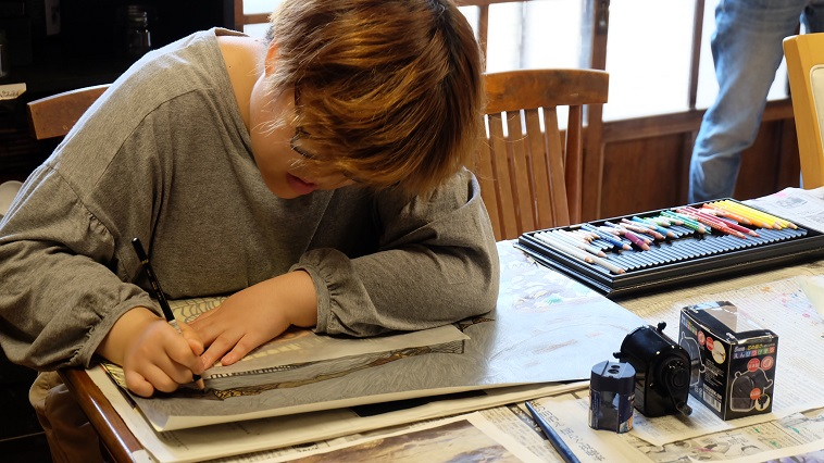 【写真】机に向かい、集中して絵を描くアンナさん。
