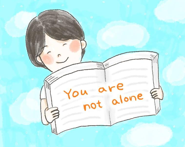 【イラスト】「You are not alone」と書いたノートを開いて見せる、さかいさん