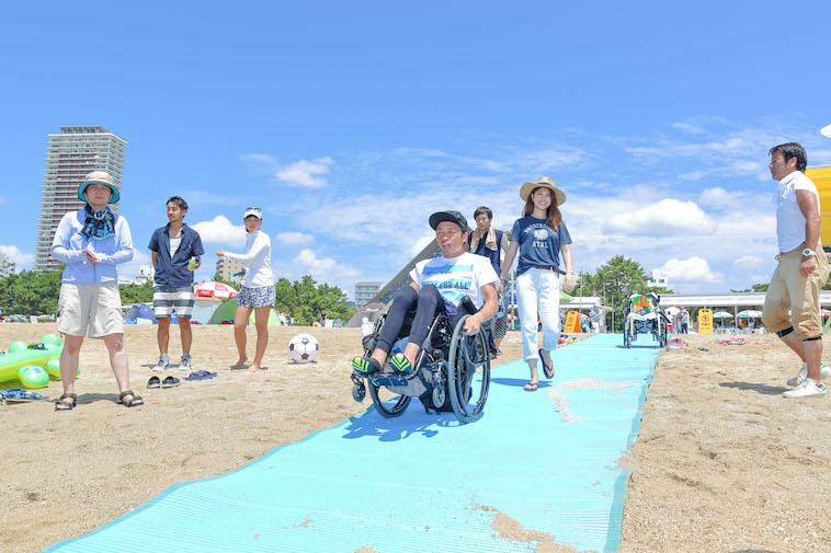 【写真】砂浜でビーチマットの上を歩くきどあやさんと車椅子に乗って移動しているきどしゅんすけさん