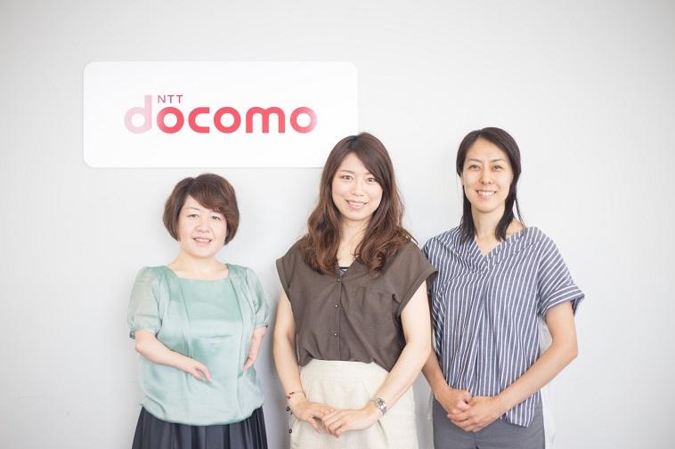 【写真】docomoの看板の前で笑顔で立っている3人の女性