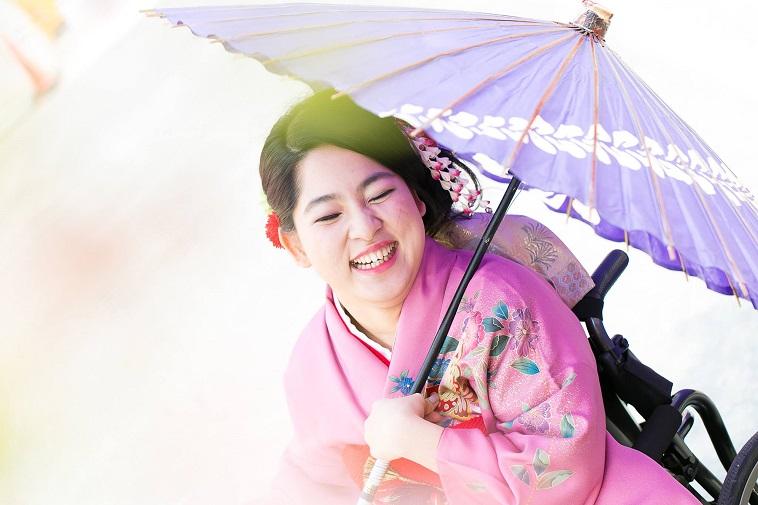 【写真】車椅子用の振袖を身につけ、満面の笑みで写る女性。
