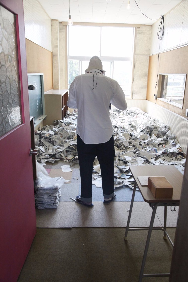 【写真】広い部屋の中で新聞をちぎる習慣があるこいけさんの後ろ姿