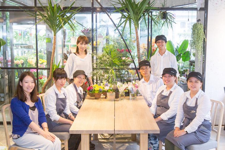 【写真】働くスタッフ8人が並んでこちらを見て微笑んでいる