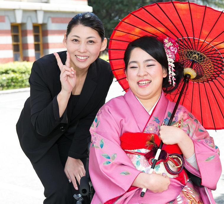 【写真】なかじまさんと振袖をきた車椅子の女性。明るい笑顔で溢れている。