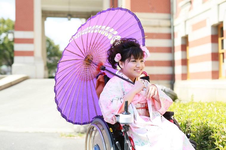 【写真】振袖を着て車椅子に座るかやまさん。笑顔でカメラに写る。