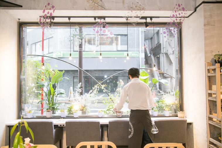 【写真】光が差し込み明るい雰囲気の店内を掃除するスタッフ