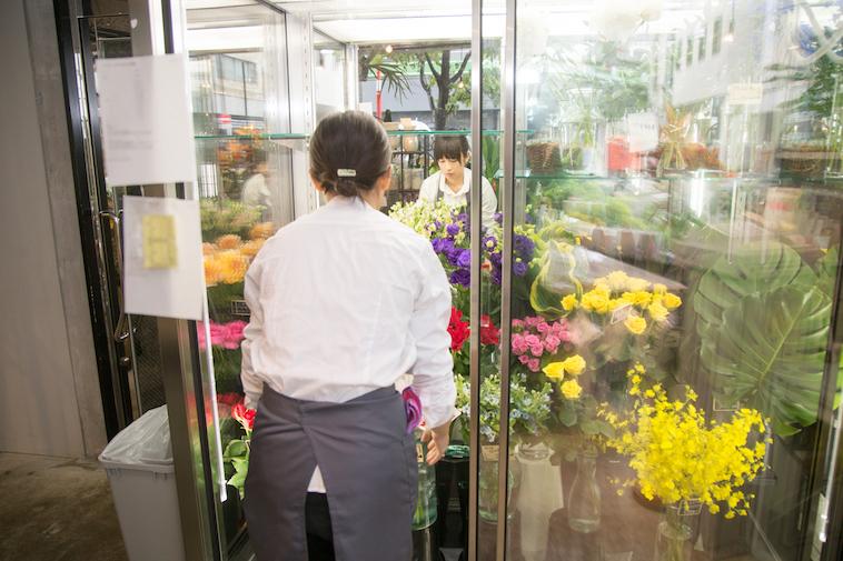 【写真】スタッフが真剣な表情で花を運んでいる