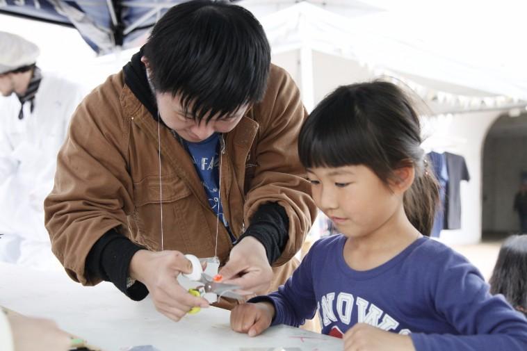 【写真】子どもにプラ板の作り方を教えるしょうへいくん