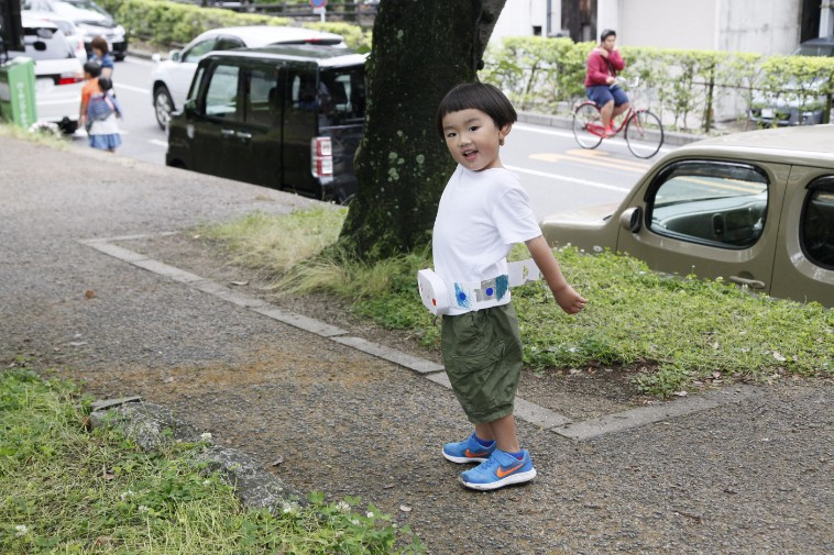 【写真】手作りのベルトをつけてはしゃいでいる子ども