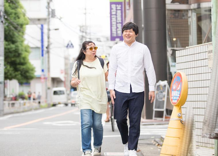 【写真】利用者のおおたさちえさんと街道を一緒に歩くすずきたかみちさん