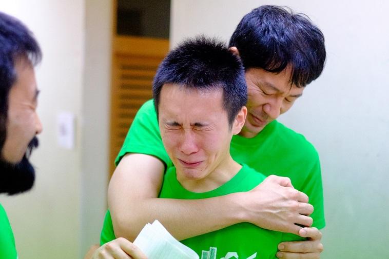 【写真】泣きそうになる高校生の男の子を抱きしめるチームメンバーの男性と、それを微笑みながら見守るもう一人のチームメンバーの男性