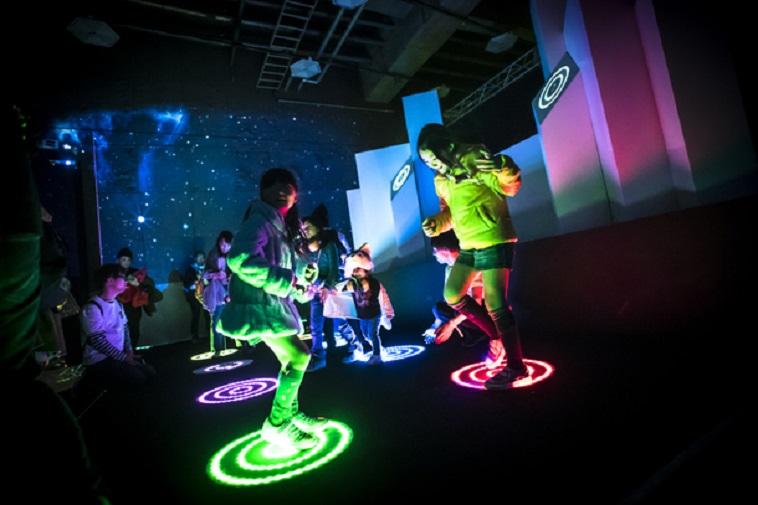 【写真】薄暗い室内の床で光る丸い輪を追いかける子どもたち。楽しそうな空気が伝わってくる。