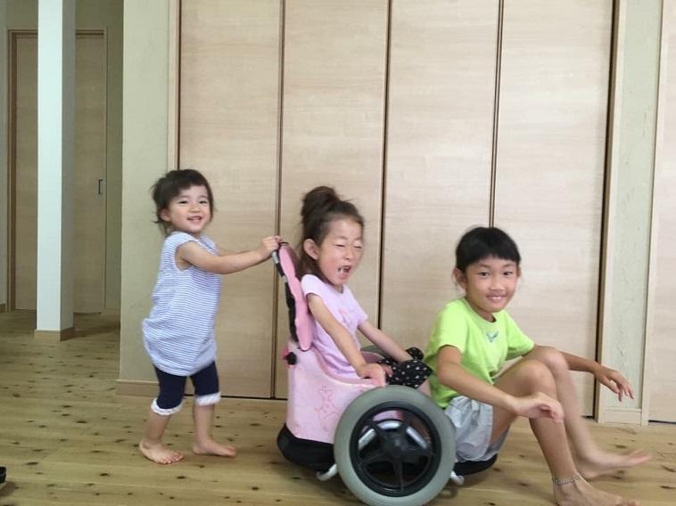 【写真】車椅子に乗る女の子と、一緒に座ろうとする女の子。そしてそれを押す女の子。3人の表情から楽しさが伝わってくる。