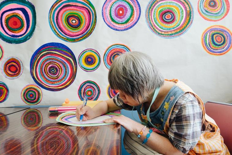 【写真】机に向かい、集中して絵を描く障害者アーティスト。