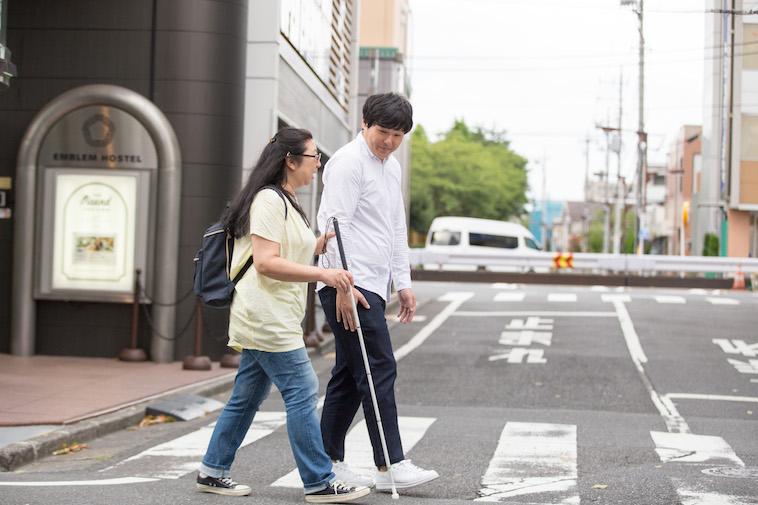 【写真】白杖を持って歩くおおたさちえさんとすずきたかみちさん