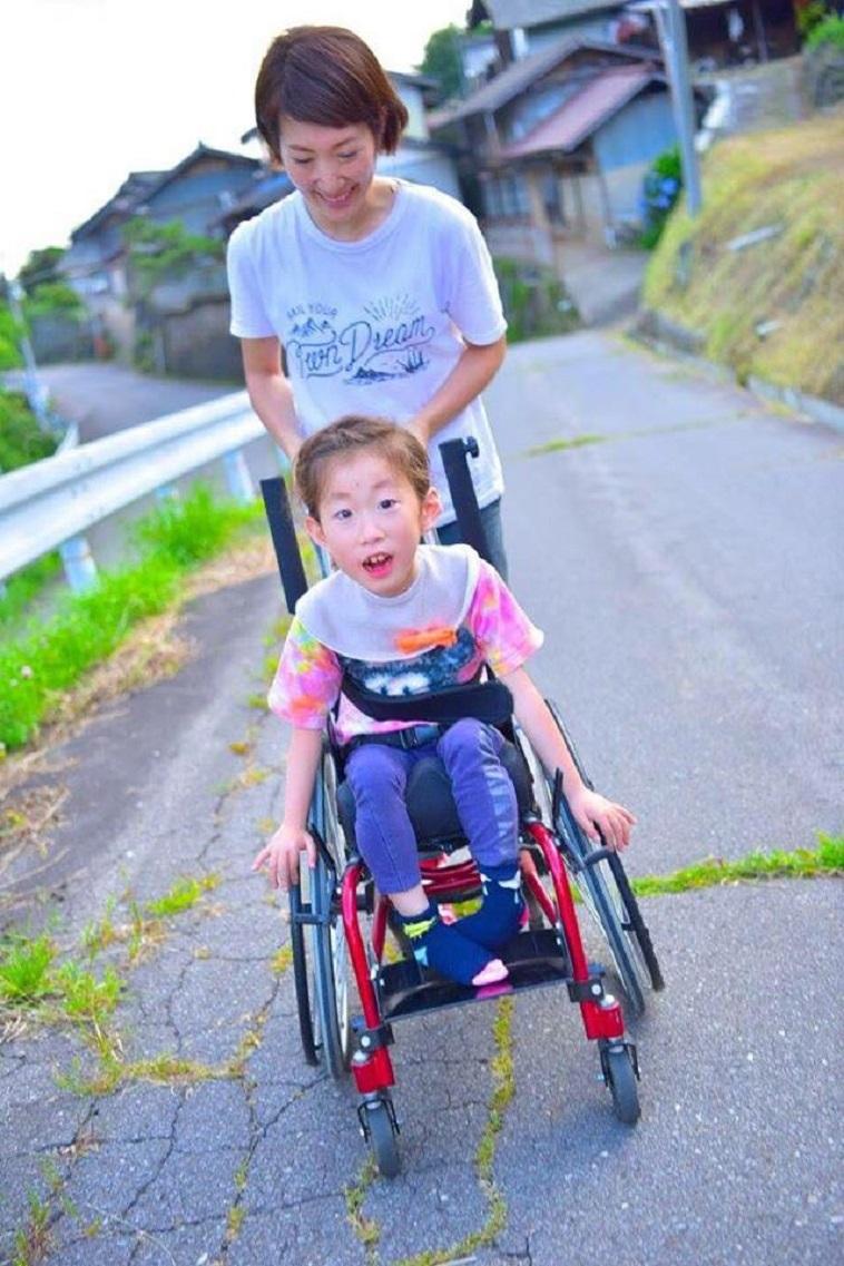 【写真】車椅子に乗るお子さんと、温かな眼差しで車椅子を押すかとうさん。