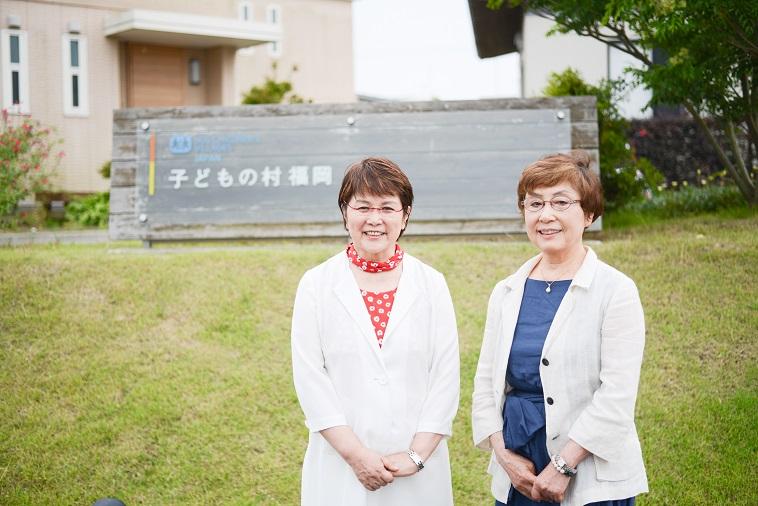 【写真】「子どもの村福岡」の看板の前で笑顔で立っているさかもとまさこさんとおおたにじゅんこさん