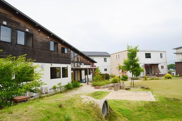 【写真】緑の草や木々がある庭の周囲に住宅がある「子どもの村福岡」