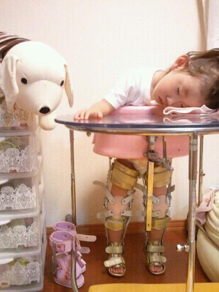【写真】装具をつけて立つ、かとうさんのお子さん。立ったまま机にうつ伏せになり、瞼を閉じている。疲れているようだ。