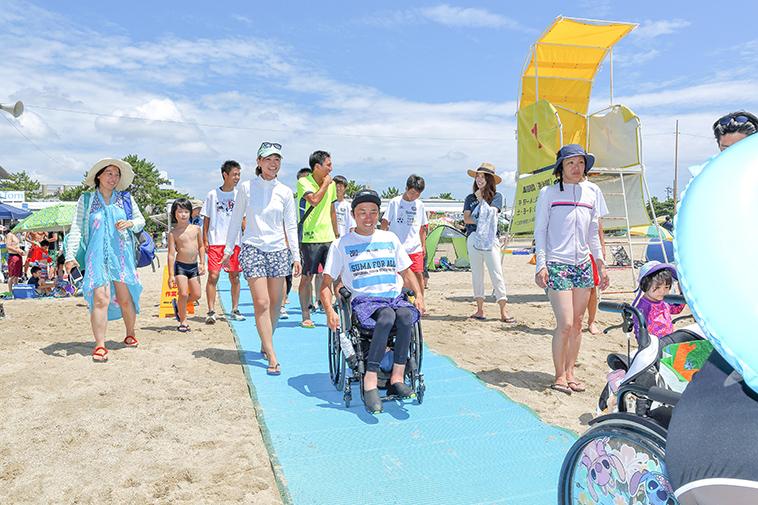 【写真】砂浜に敷いたビーチマットの上を、車椅子に乗った人々が次々に進んでいく。周囲の人々が笑顔で見守っている